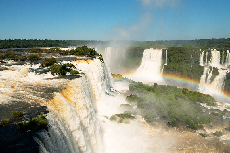 Photographed the amazing natural beauty of Iguazu Waterfall from the aerial vantage point. Breathtaking view of the Iguassu Falls, the Iguassu National Park at the borders of Argentina, Brazil and Paraguay. Extraordinary look out for a rainbow as the sun lights the tumbling waters.